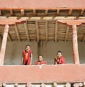 Novice child monks on balcony at monastery, Ladakh, India