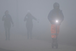 © Licensed to London News Pictures. 03/03/2021. London, UK. A member of the public rides an electric scooter on a foggy Blackheath Common in South East London. A yellow weather warning for fog is in place for parts of South East England . Photo credit: George Cracknell Wright/LNP