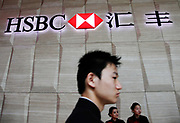 A man walks past a Hongkong Shanghai Banking Corp (HSBC) sign at the bank's new China head office in Shanghai, China, on 09 June, 2010.  Originated in Shanghai and Hongkong in 1865, HSBC is now  the world's second-largest banking and financial services group and second-largest public company according to a composite measure by Forbes magazine. It has around 7,500 offices in 87 countries and territories.