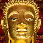 The head of a large Buddha statue at Wat Mai Suwannaphumaham.  Wat Mai, as it is often known, is a Buddhist temple in Luang Prabang, Laos, located near the Royal Palace Museum. It was built in the 18th century and is one of the most richly decorated Wats in Luang Prabang.