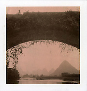Polaroid chocolate sight of a landcape through an old bridge. Wild ivy has grown on bricks along the arch. There's a man standing on top of it with karstic mountains in background. Through a frame made by a arch, mountains and river become more poetic. Guangxi province, China, Asia.