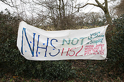 Great Missenden, UK. 18th March, 2021. A banner calling for investment in the NHS rather than HS2 is pictured close to works to fell a row of hundred-year-old oak trees in Leather Lane. Almost 40,000 people have recently signed a petition calling for the trees lining the ancient country lane not to be felled to make way for a temporary haul road and construction compound and local residents and conservationists have accused HS2 contractors of destroying active bird boxes on the site.