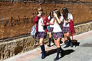 Young schoolchildren students strolling in Calle Sacramento in Leon, Castilla y Leon, Spain