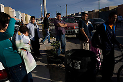 People stand outside the scene of a murder in Ciudad Juarez, Mexico.  Mexico is undergoing a violent war with the nation's drug cartels and Ciudad Juarez has become the murder capital of Mexico, with over 4,000 murders in the past two years.  President Felipe Calderon has dispatched thousands of soldiers and federal police officers in order to contain the situation, but they have not been successful.
