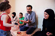 Delal and her husband and family at home. Delal walks along the narrow alleys to her temporary home in Shatila. She is a Palestinian from Damascus and now lives as a refugee in Shatila, a Palestinain camp in Beirut. She lives in Shatila with her extended family after they had to flee the war in Syria.