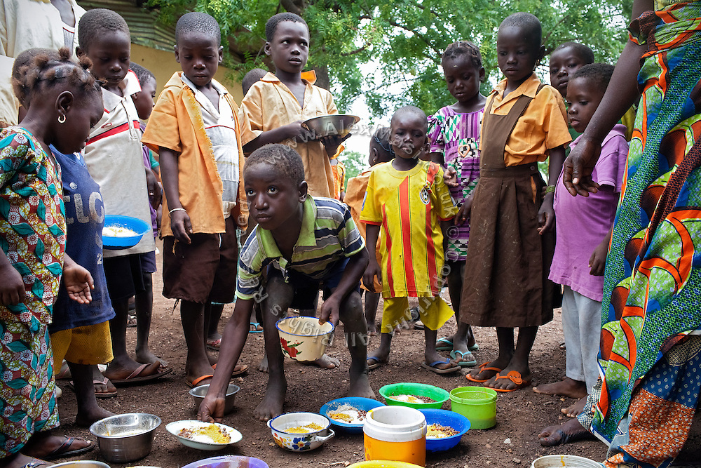 Pupils are collecting and eating nutritional meals available under the School Feeding Program run by the local NGO SEND, while in the courtyard of the small rural institution Hassana Ibrahim, 11, is attending in Boggu, Tamale, northern Ghana.