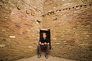 Scott Gilmore sits in a small vestibule embedded into one of the stone walls of Pueblo Bonito, Chaco Canyon, New Mexico.