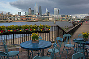 As the UK government announces further Coronavirus-related restrictions to its citizens, with the immediate closure of pubs, cafes, gyms and cinemas, and the worldwide number of deaths reaching 10,000 with 240,000 cases, 953 of those in London alone, riverside pub seating overlooking the city and the river Thames remains unused, on 20th March 2020, in London, England.