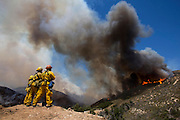Firefighters keep watch a wildfire, Friday May 31, 2013, near Castiac, California. Fourteen aircraft and more than 550 firefighter were deployed in a ground and air campaign against a brush fire that has blackened about 1,500 acres in sparsely populated San Francisquito Canyon in the Angeles National Forest northeast of Santa Clarita. The Powerhouse Fire, which broke out Thursday afternoon, was about 15 percent contained. The estimated date of full containment is Wednesday, June 5. (Photo by Ringo Chiu/PHOTOFORMULA.com)