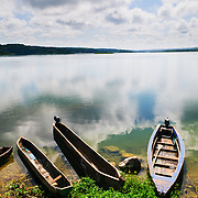 Three traditional wooden boats and canoes beached on the shore of Lake Peten Itza in Flores in northern Guatemala, with a glassy lake reflecting the clouds and sky.