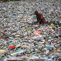 Retrieving plastic waste for recycling and resale from a river in Nairobi, Kenya
