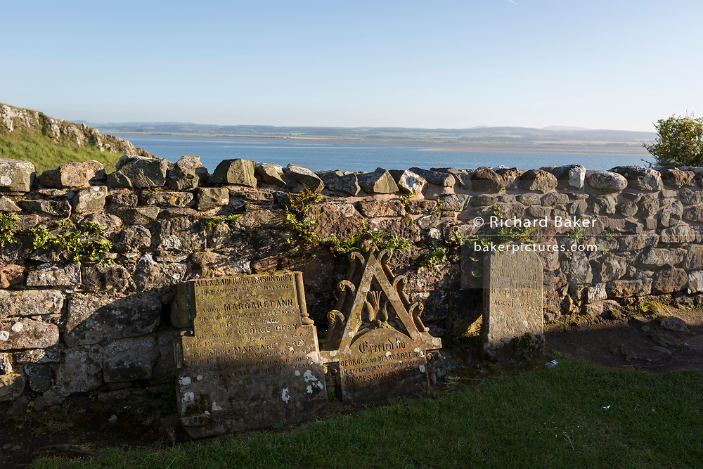 Church gravestones and the ruined monastery walls of Lindisfarne priory on Holy Island, on 27th June 2019, on Lindisfarne Island, Northumberland, England. The monastery of Lindisfarne was founded by Irish monk Saint Aidan, and the priory was founded before the end of 634 and Aidan remained there until his death in 651. The Holy Island of Lindisfarne, also known simply as Holy Island, is an island off the northeast coast of England. Holy Island has a recorded history from the 6th century AD; it was an important centre of Celtic and Anglo-saxon Christianity. After the Viking invasions and the Norman conquest of England, a priory was re-established.