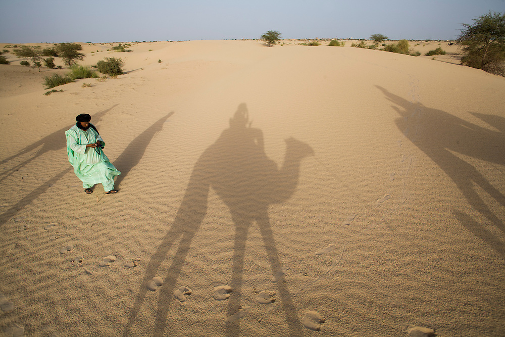 A tuareg guide with shadow of tourists riding camels in the desert around Timbuktu, in Mali.