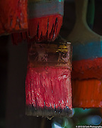 Colorful red paint brushes hang from the porch of The Art Shack in Locke, California