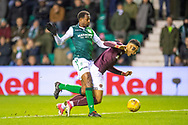 Sean Clare (#9) of Heart of Midlothian goes down in the box under pressure from Efe Ambrose (#25) of Hibernian FC during the Ladbrokes Scottish Premiership match between Hibernian FC and Heart of Midlothian FC at Easter Road Stadium, Edinburgh, Scotland on 29 December 2018.