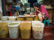 29 SEPTEMBER 2015 - BANGKOK, THAILAND:  A woman sorts and grades peanuts in her market stall near Saphan Lek market. Street vendors and illegal market vendors in the Saphan Lek area will be removed in the next two weeks as a part of an urban renewal project coordinated by the Bangkok Metropolitan Administration. About 500 vendors along Damrongsathit Bridge, popularly known as Saphan Lek, have 15 days to relocate. Vendors who don't move will be evicted. Saphan Lek is just one of several markets and street vending areas being closed in Bangkok this year. The market is known for toy and replica guns, bootleg and pirated DVDs and CDs and electronic toys.   PHOTO BY JACK KURTZ