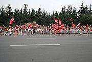 A crowd waits by a street to watch a runner carry the Olympic Torch in a relay in the southern city of Wuhan.