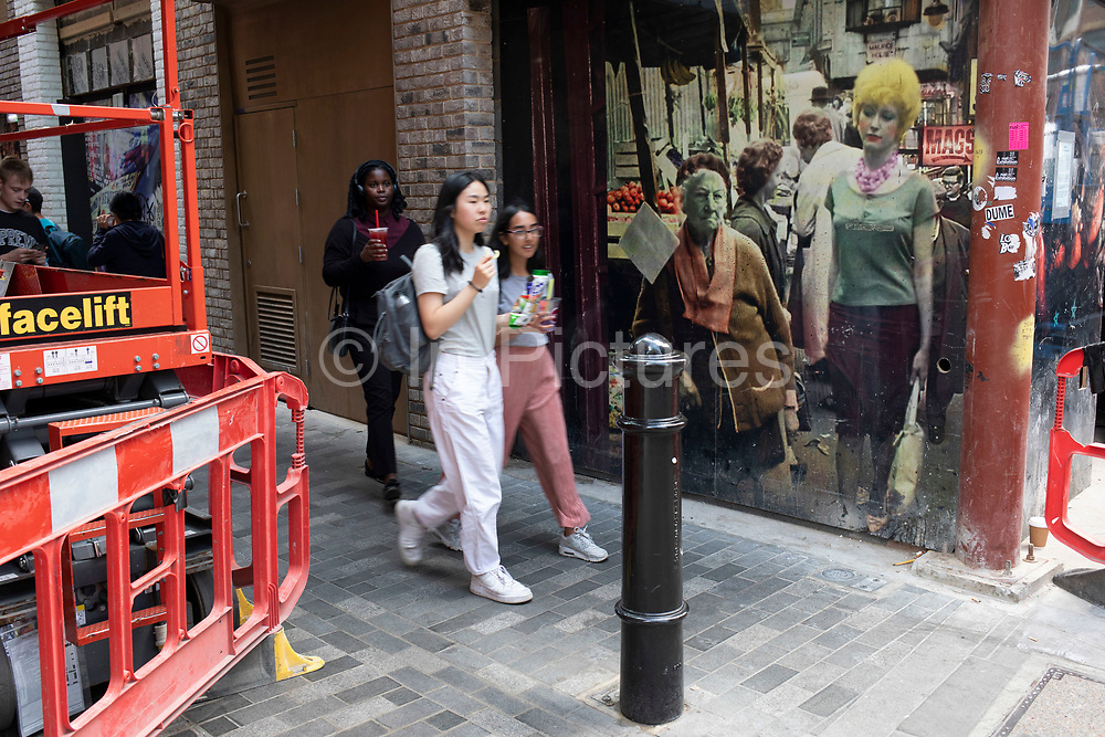 Pictures of white British people looking on to multicultural passers by and redevelopment in Soho, central London, United Kingdom. In Walker's Court, this seedy alley, there were once sex shops, DVD shops, live sex shows and all manner of pornographic offerings, but now it is all but closed and being redeveloped and gentrified. Walkers Court is a pedestrian street in the Soho district of the City of Westminster. The street dates from around the early 1700s and escaped modernisation in the late nineteenth century so that it retains its original narrow layout. In the twentieth century the small shops that traded from the street gradually closed and from the late 1950s the street became associated with Sohos sex trade.