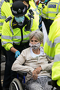 Metropolitan Police officers arrest a disabled climate activist from Extinction Rebellion who had occupied a road around Parliament Square during a Back The Bill rally on 1st September 2020 in London, United Kingdom. Extinction Rebellion activists are attending a series of September Rebellion protests around the UK to call on politicians to back the Climate and Ecological Emergency Bill (CEE Bill) which requires, among other measures, a serious plan to deal with the UK's share of emissions and to halt critical rises in global temperatures and for ordinary people to be involved in future environmental planning by means of a Citizens' Assembly.