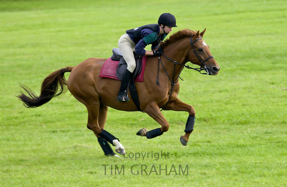 Young male rider competing at cross country horse event Cotswolds, Oxfordshire, UK