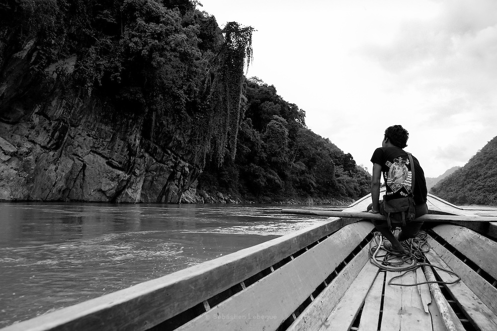 Thailand, Salween river  Pochi, a young man seat on the row in the front of the long tail boat  FR   Pochi, un jeune homme est assis sur une rame à lavant de lembarcation.