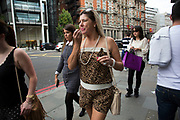 Fashion in Knightsbridge, London, UK. This is a particularly wealthy part of West London and this is highly visible on the streets. Here a woman applies her lip gloss while walking along, wearing leopard print top and shorts outfit.