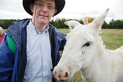 Man with learning disability on trip to farm stroking a donkey