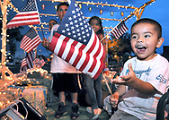 Robin Zielinski/Sun-News<br /> Jacob Lopez, 3, gets excited when handed an American Flag while riding in the Lopez Glass float on Wednesday during the city Electric Light Parade. Standing in the background from left to right is Samuel Provencio, 8, Marcuss Flores, 7, and Aubre Lopez, 9. For a photo gallery of Fourth of July festivities visit our web site at lcsun-news.com.