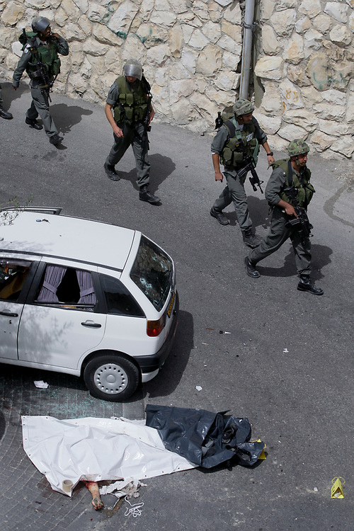Israeli Police officers at the scene where a Palestinian man was killed by Israeli police after he tried to drive into a checkpoint near Sur Baher in east Jerusalem, on April 7, 2009. The incident took place shortly after police demolished the house of Hussam Dwayyat, who went on a rampage in Jerusalem's busy Jaffa Street in June. Smashing vehicles and overturning a bus with his machinery, he killed three people and injured 45 others, before he was shot dead.