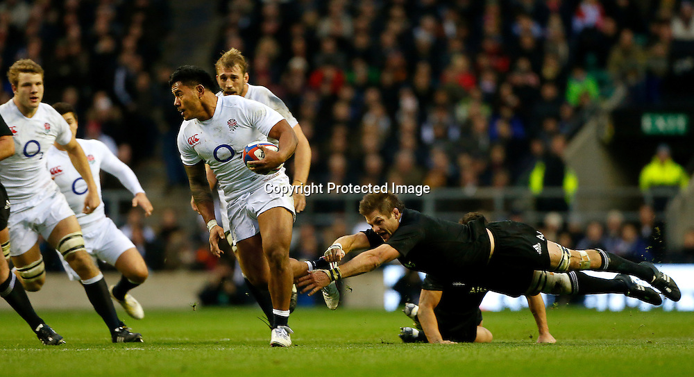 epa03493219 Manusamoa Tuilagi of England (C) in action against Richie McCaw of New Zealand (R) during their Rugby Union QBE Internationals match between England and New Zealand at Twickenham Stadium in London, Britain, 01 December 2012.  EPA/KERIM OKTEN