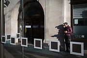 A Londoner and squares on the glass screens at a bus stop in Kingston, on 7th November 2019, in London, England.