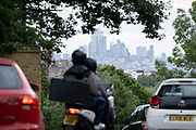 With the skyscrapers of the City of London, the capitals financial district, in the distance, motorists in morning rush-hour traffic, turn down Sydenham Hill, on 15th June 2021, in south London, England.