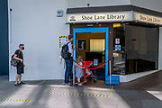 Library users wait to safely enter Shoe Lane Library during the Coronavirus pandemic in the City of London, the capital's financial district, on 6th August 2020, in London, England.