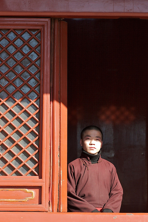 A young monk stands at the window of Yonghegong's smaller rooms March 7, 2007.  This Tibetan Temple is known to tourists as Lama Temple and it's located in Dongcheng District Beijing, China. This is the largest Temple of its kind outside of Tibet.  In 1723 the structure was turned into a Temple after the resident became the third Qing Emperor.