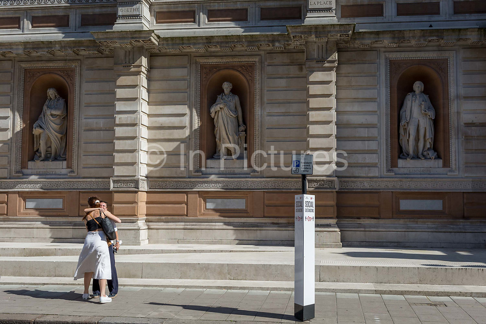With a further 184 reported UK Covid deaths in the last 24 hrs, a total now of 43,414, old friends ignore lockdown rules when greeting each other with a hug infront of the statues of Gottfried Leibniz, Georges Cuvier and Carl Linnaeus, and alongside a social distance post outside the Royal Academy on Burlington Gardens, on 26th June 2020, in London, England. Government restrictions have yet to ease when the 2 metre rule is to be relaxed on 4th July for one metre plus and when art galleries like the RA re-open. Venues re-opening will be conditional on the progression of the virus and how well social distancing measures are implemented.