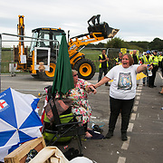 13 local activists locked themselves in specially made arm tubes to block the entrance to Quadrilla's drill site in New Preston Road, July 03 2017, Lancashire, United Kingdom. Michellemartin and friend left behind police lines amongst the demolition. The 13 activists included 3 councillors; Julie Brickles, Miranda Cox and Gina Dowding and Nick Danby, Martin Porter, Jeanette Porter,  Michelle Martin, Louise Robinson,<br />