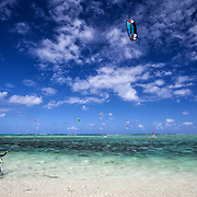 Kite surfing along the coast at Le Morne Brabant, Mauritius. Dozens of kite surfers flock to this spot everyday and tourists can take lessons.