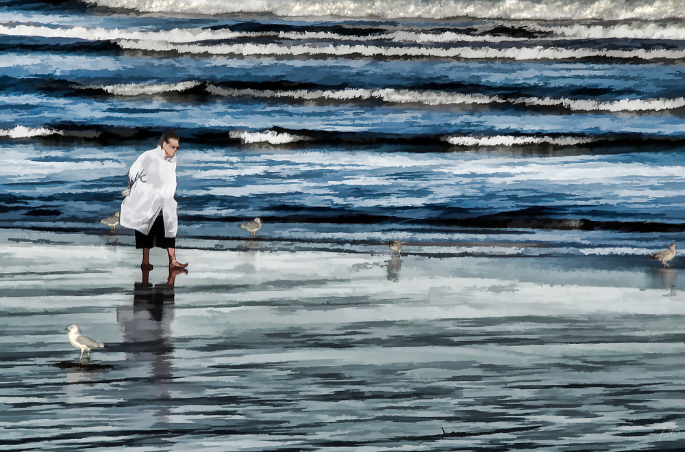 Walking in the water at the shoreline,barefoot on a cold, late fall day, surrounded by seagulls.