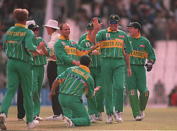 South Africa captain Hansie Cronje (centre) goes on his knees to Pat Simcox (second right) after he ran out England's Alec Stewart with a direct hit