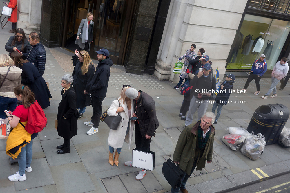 Surrounded by other shoppers and passers-by, a romantic couple kiss in the street, on 28th October 2019, in Westminster, London, England.