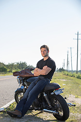 good looking man sitting against a parked motorcycle on a rural road