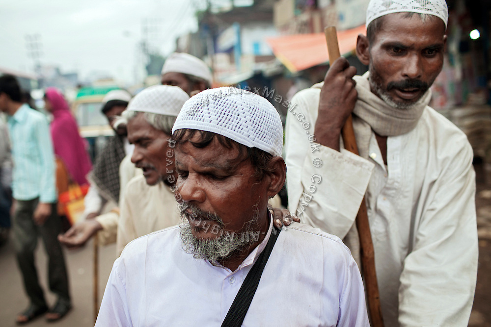 During the holy month of Ramadan, blind Muslim beggars are waling in line in Kasi Camp, one of the nineteen water-affected colonies surrounding the abandoned Union Carbide (now DOW Chemical) industrial complex in Bhopal, Madhya Pradesh, India.