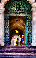 """""""Pontifical Swiss Guard that protects the Sisters and the bronze doors of the Vatican""""…<br /> <br /> My Roman tour guide at the Vatican, who knew all who worked there, made sure he presented every opportunity for me knowing I was a photographer.  For this and several other images, he talked with security allowing me to enter areas off limits to photograph through doorways and windows.  This huge bronze door has been the official entrance to the apostolic palace since 1663, and is permanently watched by three Swiss guards. The Pontifical Swiss Guard was founded in 1506 and in the 18th century several Swiss soldiers were recruited from various European courts to form the close quarter guards of the kings. Michelangelo designed the official--highly colorful--uniform, and guards also wear a long sword and a traditional halberd. The bronze door opens to a long corridor leading to the famous steps of the Scala Regia, which was designed by Bernini to appear longer and wider than in actuality. Unfortunately, this architectural wonder is closed to visitors, as is the rest of the apostolic palace where the pope lives; only official visitors are admitted inside."""
