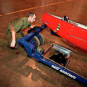 Member of the Blues, the support of the 'Red Arrows', Britain's Royal Air Force aerobatic team jacks up tow-bar in hangar