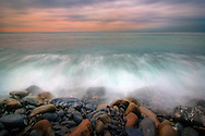 The pebbles beach of Riomaggiore at dawn. The first lights of the rising sun peeping through some deep stormy clouds. Taken on an early and cold morning on January. A long exposure time was used to blur the water and clouds.