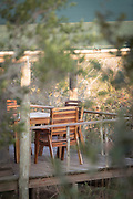 View of sitting area by tent in forest at Mhlumeni Bush Camp, Eswatini