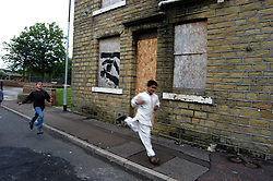 Children running along a street in a deprived area of Halifax; Yorkshire, Boarded up houses in background