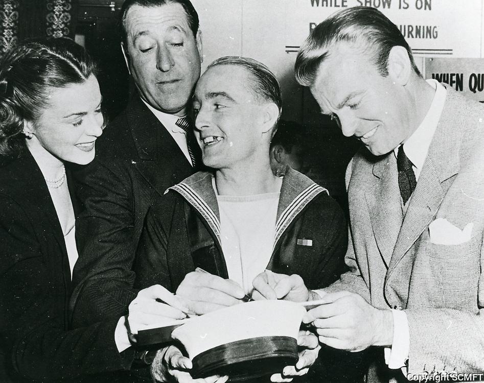 1944 Marguerite Chapman, Arthur Treacher and Dennis O'Keefe sigh autographs for a sailor at the Hollywood Canteen