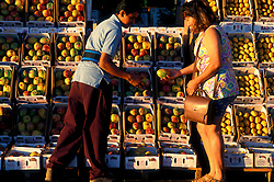 Stock photo of a woman buying a mango from a man at the farmer's market in Houston Texas