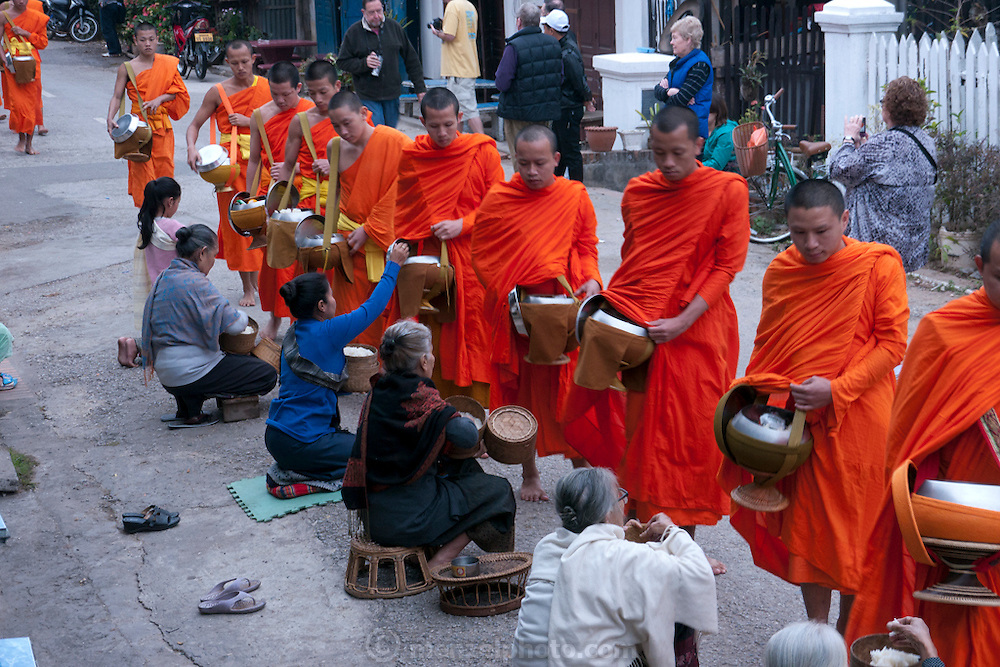 """Luang Prabang, Laos. Every morning at dawn, barefoot Buddhist monks and novices in orange robes walk down the streets collecting food alms from devout, kneeling Buddhists. They then return to their temples (also known as """"wats"""") and eat together. This procession is called Tak Bat, or Making Merit. ."""
